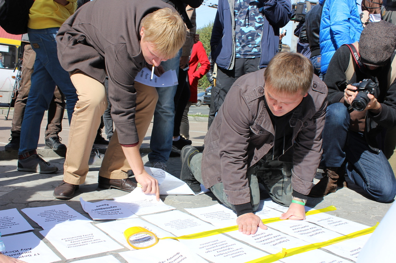 Пікетувальники прикріплюють інформаційні листівки під посольством РФ