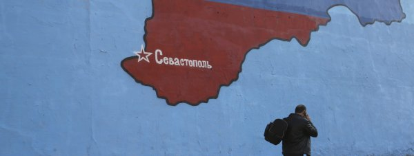 """A man passes a mural showing a map of Crimea in the Russian national colours on a street in Moscow March 25, 2014. NATO's top military commander said on Sunday Russia had built up a """"very sizeable"""" force on its border with Ukraine and Moscow may have a region in another ex-Soviet republic, Moldova, in its sights after annexing Crimea. The map shows the location of the city Sevastopol. REUTERS/Artur Bainozarov (RUSSIA - Tags: POLITICS CIVIL UNREST)"""